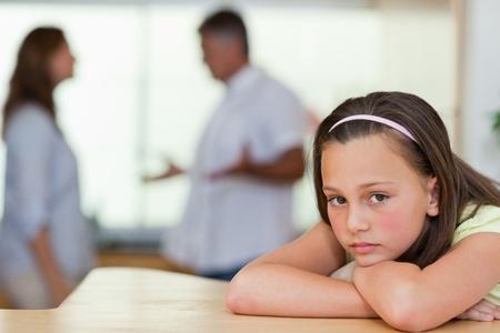 Trauriges Mädchen mit ihren kämpfenden Eltern hinter ihr