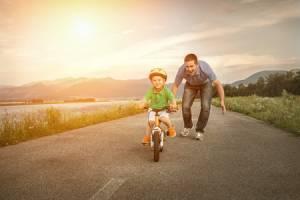 Glücklicher Vater mit Sohn auf dem Fahrrad im Freien