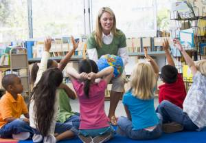 Kindergärtnerin und Kinder mit erhoben Händen in Bibliothek